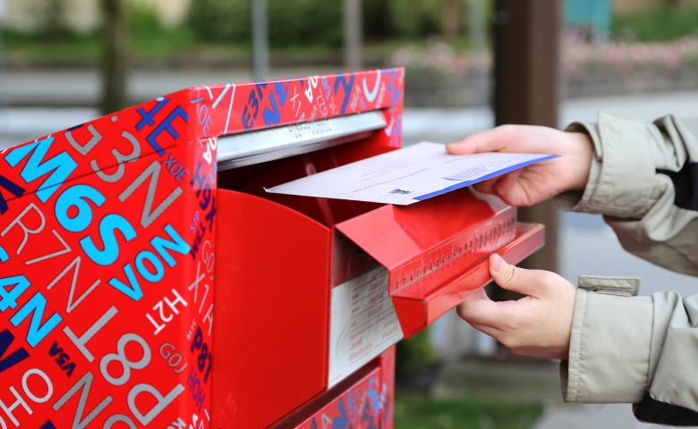 Person mailing a letter in a Canada Post mailbox