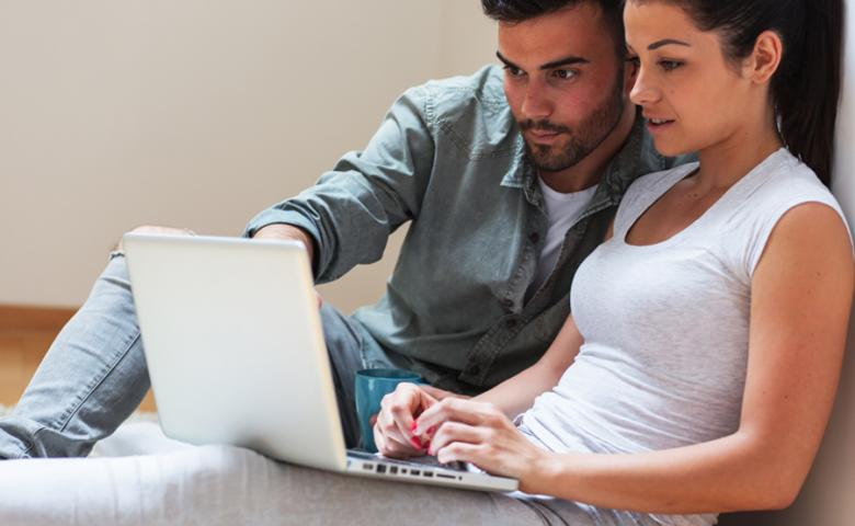 Couple sitting on floor and using laptop